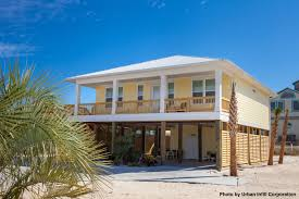 raised home right on the beach with yellow siding and a wrap raised home right on the beach with yellow siding and a wrap around deck