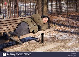 homeless man sleeping on park bench on cold winter day stock photo