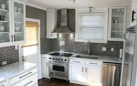 black backsplash glass subway tile in kitchen and white cabinets