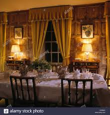 yellow curtains on window in paneled country dining room with