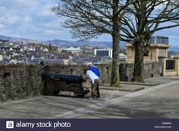 siege canon tourists examine siege canon on derry walls overlooking the stock