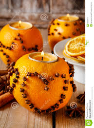 orange pomander with candle decorated with cloves in