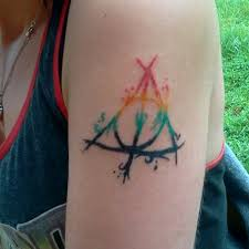 nice colored deathly hallows tattoo on left shoulder