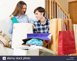 happy couple with clothes and shopping bags in home interior stock happy couple with clothes and shopping bags in home interior