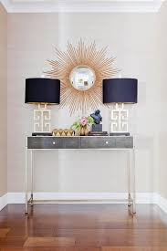 gold and gray foyer features a gold sunburst mirror over a gray