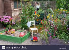 childrens play area in a busy garden of raised flower beds stock