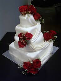wedding cake hashtags bright roses intertwined around a white 4 tier fondant draped