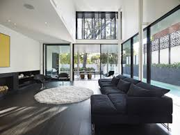 modern glasses windows large tiles living room with black sofas