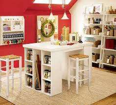 delectable home art room with white crafting table and red walls