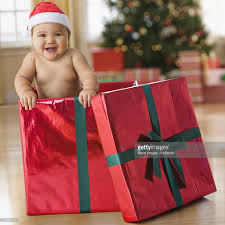 mixed race baby boy playing in christmas gift box stock photo
