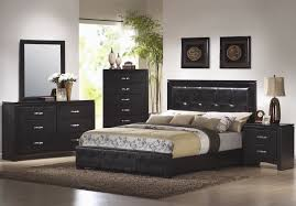 black bed with wall and gray floor also glass windows white table