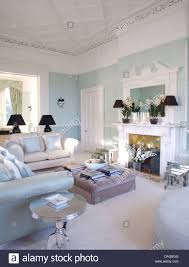 white and pale blue sofas around gray velvet ottoman in front of