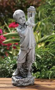 boy holding firefly jar solar garden statue 18 25 inches from