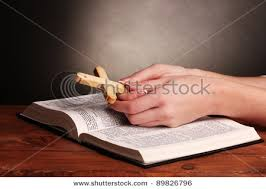 of a holding the cross and praying an open bible in