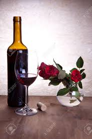 bottle and glass with red wine and beautiful red roses stock photo