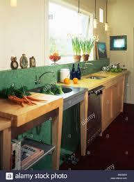 free standing kitchen sink cupboard bunch of carrots on freestanding unit beside steel sink in