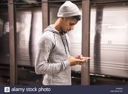 a candid portrait of a young black man using his phone in new