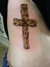 wooden cross tattoo on man side rib
