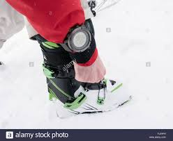skier adjusting alpine touring ski boots and wearing a suunto