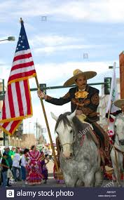 a mexican vaquero cowboy carries the american flag on horseback
