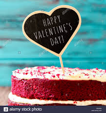 closeup of a red velvet cake topped with a heart shaped chalkboard