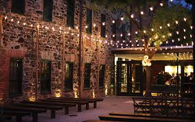 party venues in baltimore this outdoor ceremony with wooden benches and cafe lights at