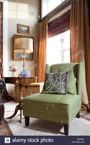 green classic armchair by a window in an american contemporary