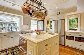 white kitchen with white granite tops island and hanging pot