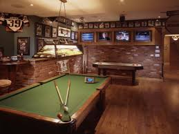 country man cave design with green pool table with som stick also