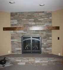 brown polished wooden mantel shelf with grey stone fireplace