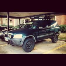off road lifted honda crv with roof rack and black stock rims