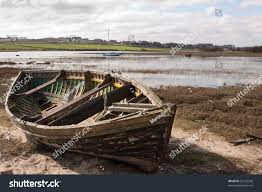 stock photo an old rowing boat in need of repair on the beach by