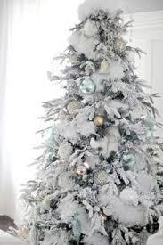 white garland decorating white on white christmas tree with woodland