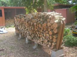 diy outdoor firewood rack with cinder block base in the backyard