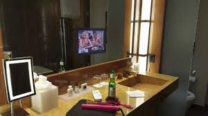 bathroom with makeup mirror stool and built in mirror tv a