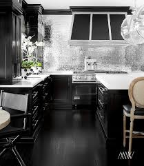 black kitchen features black cabinets paired with white marble