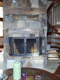 hand crafted stone fireplace remodel with hand forged iron doors