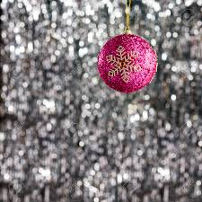 pink christmas bauble over silver glitter background stock photo