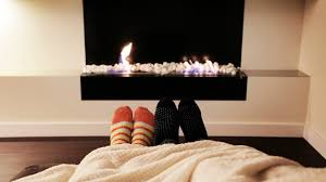 couple feet in socks by fireplace man and woman relaxing by warm