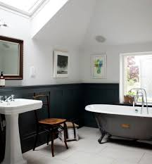 bathroom with black wainscoting and clawfoot freestanding tub