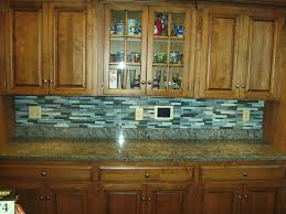 the glass tile backsplash along the edges of this granite counter