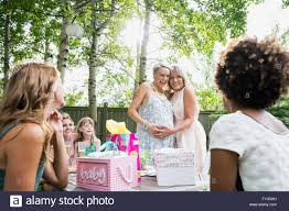 mother and pregnant daughter hugging backyard baby shower stock