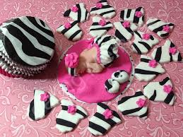 baby in a zebra print tutu set cake topper and cupcakes