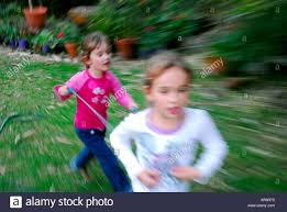 two children playing horse running on backyard lawn stock photo