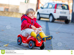 kid play car funny little kid boy driving toy car outdoors stock photo image