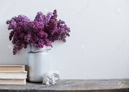 home interior decor bouquet of lilacs in a vase and books on