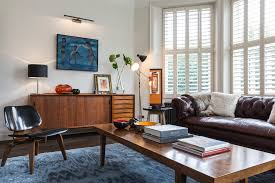 eames sofa living room midcentury with white plantation shutters