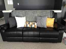 Sofas With Pillows by Lighten Up A Black Leather Couch With Bright Pillows And A Throw