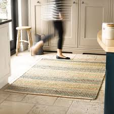 rug care guide how to look after your rug the rug seller a natural fiber rug placed in a kitchen with a lady walking over it be