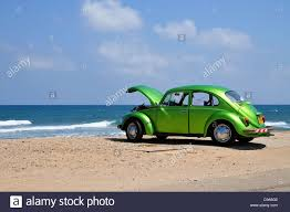 volkswagen beetle green a green 1969 volkswagen beetle on the beach stock photo royalty